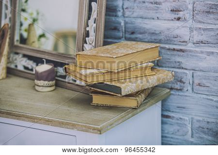 Books Stack On The Old Table In The Background Of Mirrors, Candles.