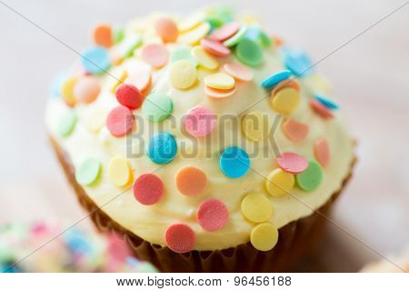 food, junk-food, culinary, baking and holidays concept - close up of glazed cupcake or muffin on table