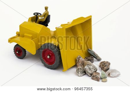 Yellow toy tipper truck and stones