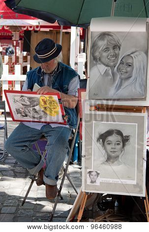 Parisian Artist Drawing A Caricature In Montmartre Of Paris