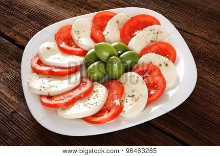 Mozzarella Cheese Slices With Tomatoes And Olives.