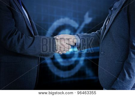 Close up on two businesspeople shaking hands against digital target