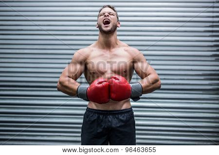 Muscular boxer screaming in crossfit gym