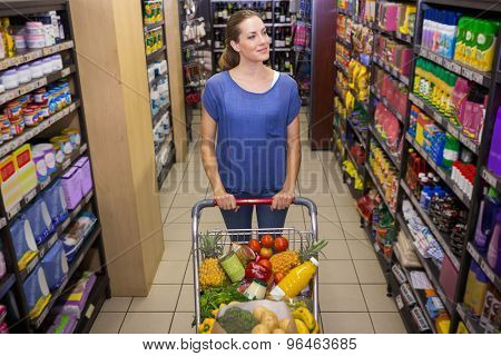 Pretty woman pushing trolley in aisle at supermarket
