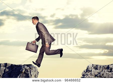 Businessman jumped over abyss