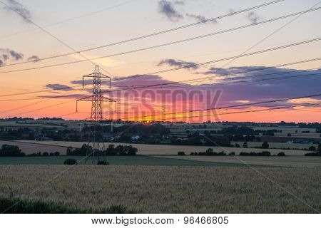 sunset shot of electricity pylon in field
