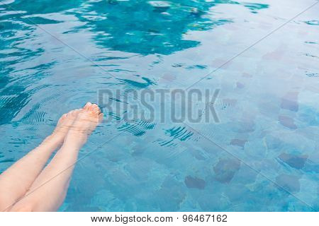 Female legs in the swimming pool water