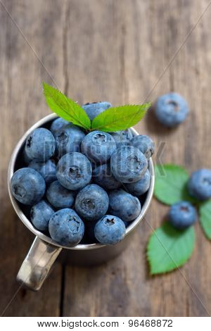 Metal cup and Blueberry on old wood