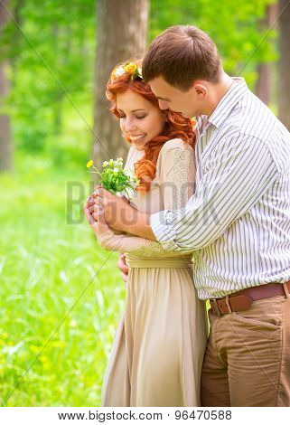 Handsome guy giving to her precious girlfriend bouquet of wildflower, spending date in the park, enjoying romantic relationship
