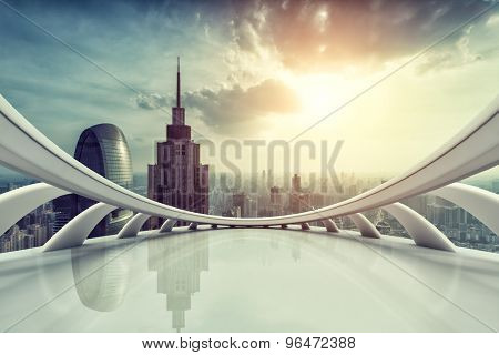 Modern city skyline with empty indoor floor at sunset