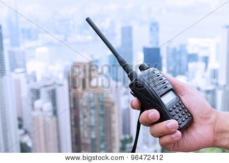 hand holding walky talky with cityscape as background