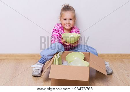 Little girl with dishware on the floor
