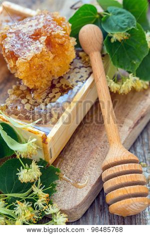Honey Comb And A Wooden Spoon.