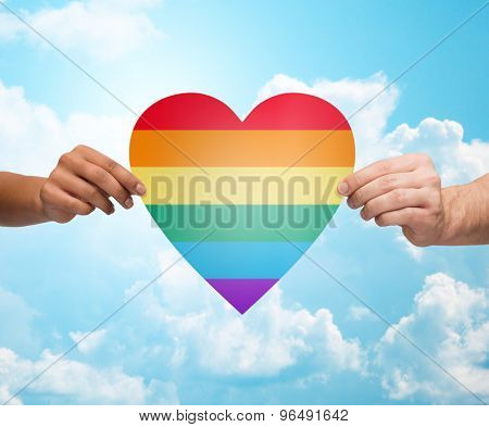 people, gay pride, gesture and homosexual concept - close up of couple hands holding rainbow heart shape over blue sky