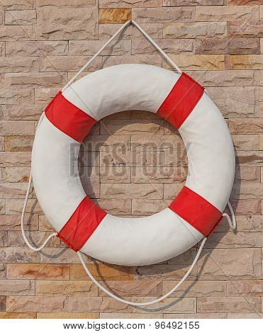 The White And Red Life Buoy Hanging On The Brick Wall Around The Swimming Pool, For Safety And Rescu