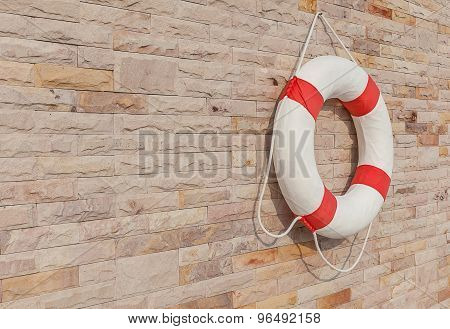 The White And Red Life Buoy Is Hanging On The Brick Wall Around The Swimming Pool, For Safety And Re