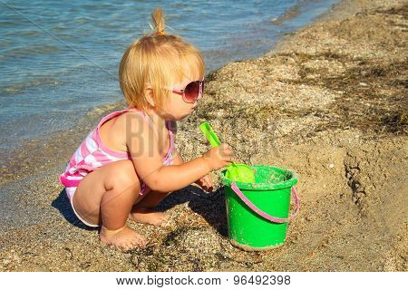 Little girl playing on the beach with pail and shovel. A child age 1 year builds sand pies.