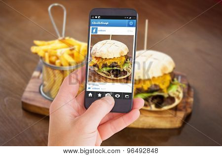 Female hand holding a smartphone against close up on a cheese burger and french fries