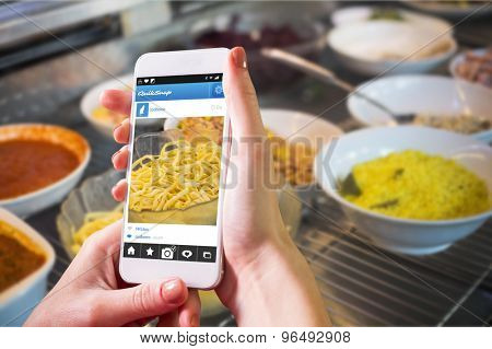 Hand holding smartphone against delicious bowls of fresh salads
