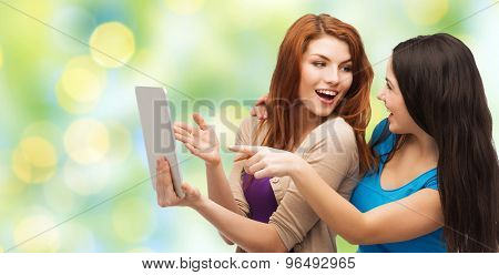 technology, friendship and people concept - two smiling teenage girls or young women pointing finger at tablet pc computer over green lights background