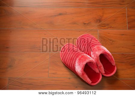 Pair Of Pink Slippers On A Wooden Floor