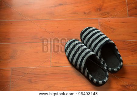 Pair Of Black Slippers On A Wooden Floor