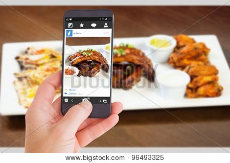 Female hand holding a smartphone against close up on a platter of finger food for a party