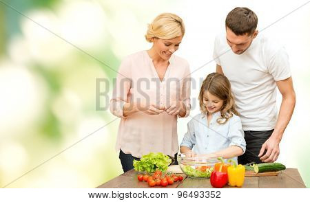 vegetarian food, culinary, happiness and people concept - happy family cooking vegetable salad for dinner over green natural background