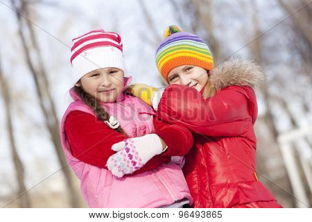 Two cute girls having fun in winter park