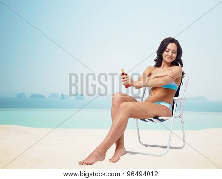 people, tanning, skincare, summer and beach concept - happy young woman in bikini swimsuit sunbathing on folding chair and applying sunscreen to skin over infinity edge pool at hotel resort background