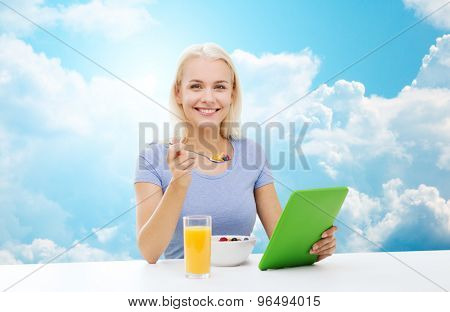 healthy eating, dieting and people concept - smiling young woman with tablet pc computer eating breakfast over blue sky and clouds background