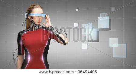 people, technology, future and progress - young woman with futuristic glasses and microchip implant or sensors over gray background with grid and squares