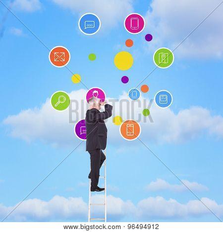 Mature businessman standing on ladder against sky