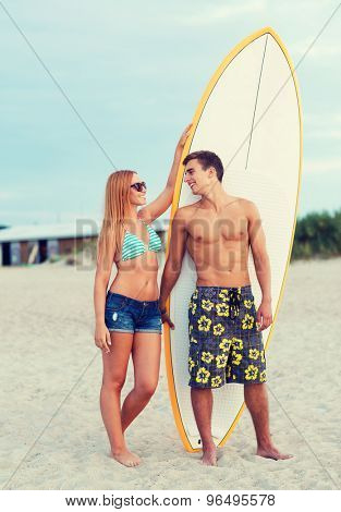 friendship, sea, summer vacation, water sport and people concept - smiling couple in swimwear and sunglasses with surfs on beach