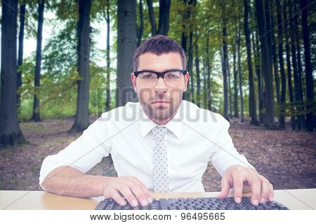 Businessman working at his desk against tree trunks in the forest