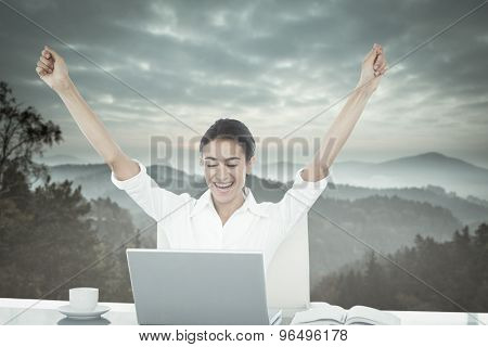 Businesswoman celebrating a great success against trees and mountain range against cloudy sky