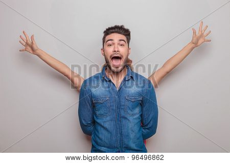 Young casual man screaming while his girlfriend is holding her hands up behind him.