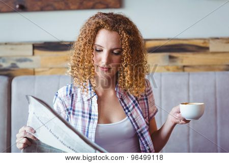 Pretty curly hair girl having cup of coffee and reading newspaper at the cafe