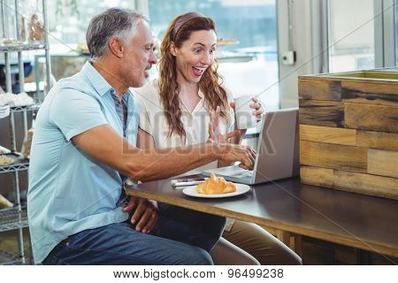 Happy couple watching something funny on laptop in the bakery store
