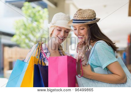 Two happy women looking at shopping bags in shopping mall