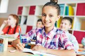 foto of schoolgirls  - Cute schoolgirl looking at camera with smile at lesson - JPG