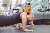 Постер, плакат: Personal trainer encouraging muscle man in push ups training