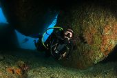 stock photo of cave woman  - Female Scuba Diver exploring underwater reef and caves - JPG