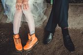 stock photo of woman boots  - Legs of a man and a woman in orange and black boots - JPG