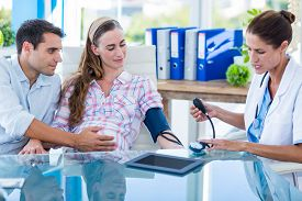 picture of gynecological exam  - Doctor taking the blood pressure of a pregnant patient with her husband in an examination room - JPG