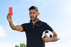 picture of referee  - Portrait of referee with a ball showing red card and whistling - JPG