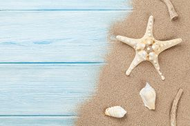 picture of starfish  - Sea sand with starfish and shells on wooden table - JPG