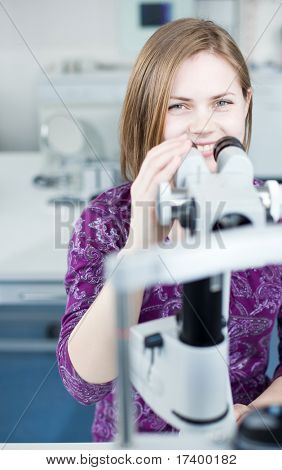 optometry concept - portrait of a young pretty optometrist using slit lamp, checking her patient's sight (color toned image)