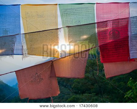 Setting Sun Shining Through Colorful Prayer Flags With The Himalayan Mountains In The Back