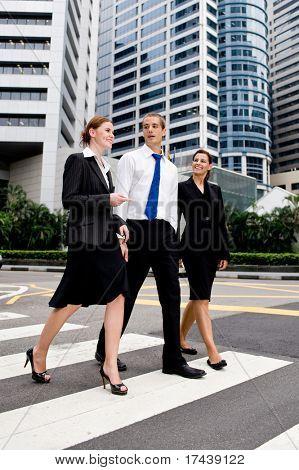 Three business people crossing road on zebra crossing